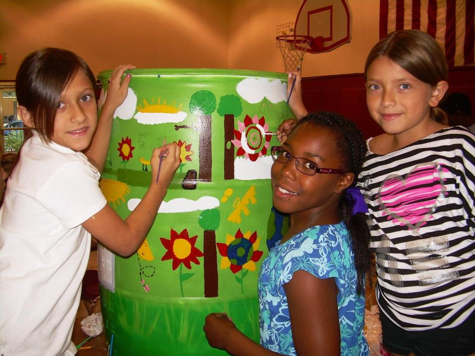 Kids painting a rain barrel